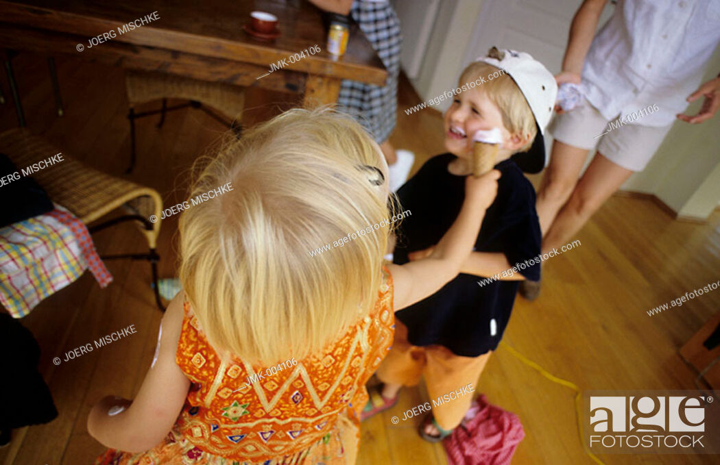 Stock Photo: A little boy and a little girl, 1-5 years old, indoor, bedaubing each other with ice cream.