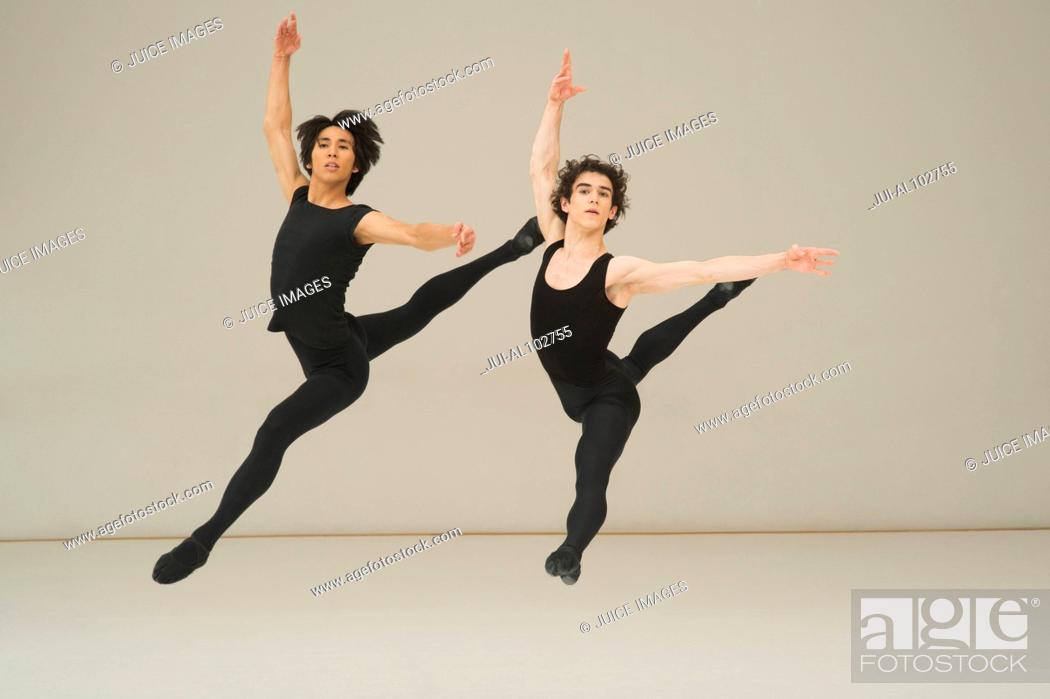 Imagen: Two young male ballet dancers leaping in the air.