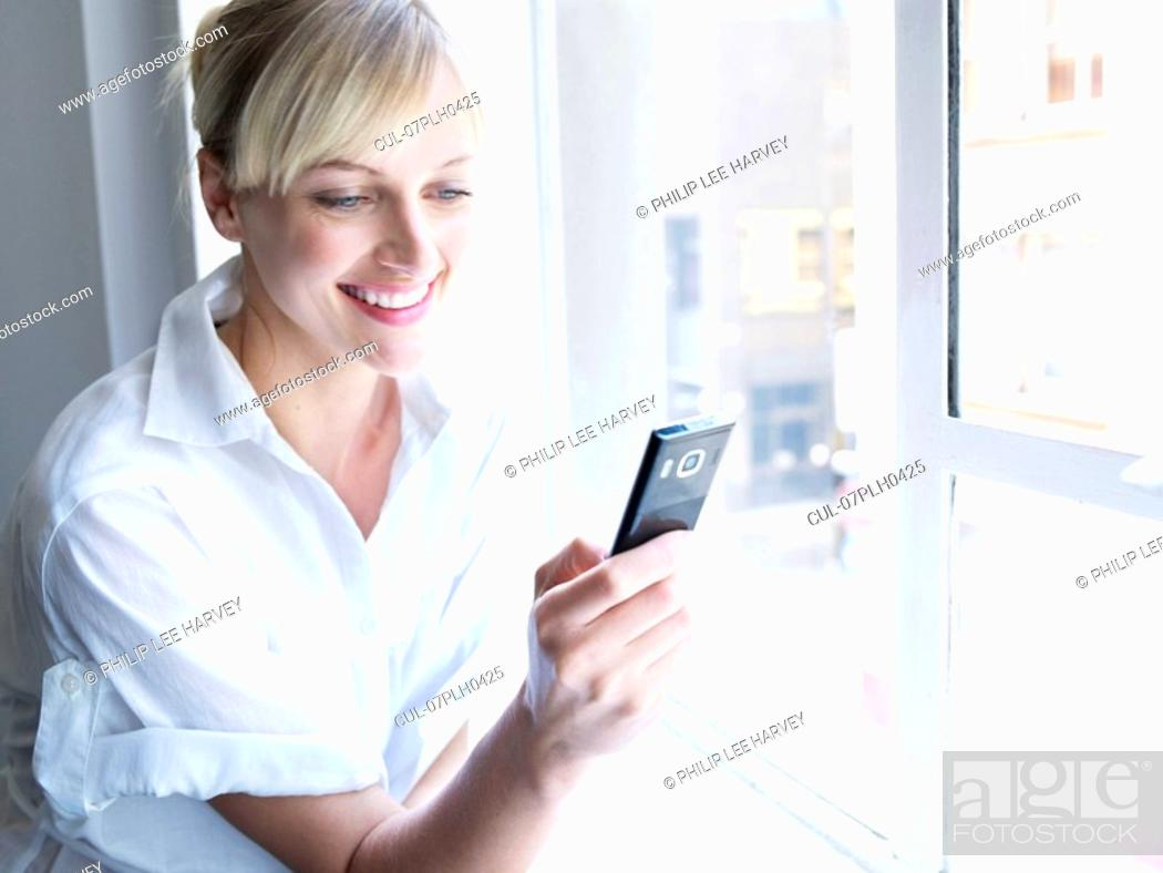 Stock Photo: Woman against window on phone.