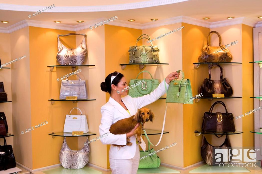 Stock Photo: Young woman looking at green designer handbag in glamorous boutique, carrying dog, side view.