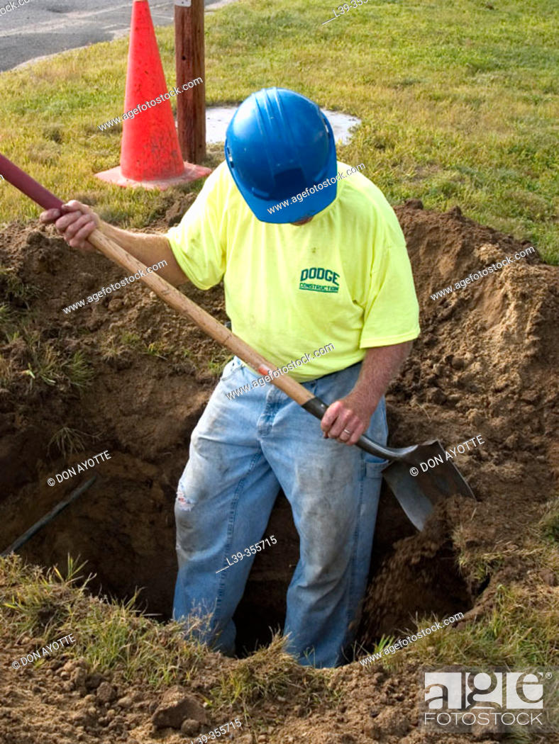 Stock Photo: Worker digging a ditch.