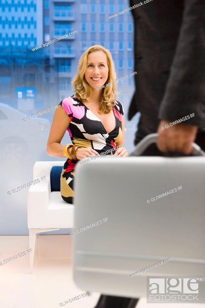 Stock Photo: Mature woman sitting on a couch and looking at a man carrying a briefcase.