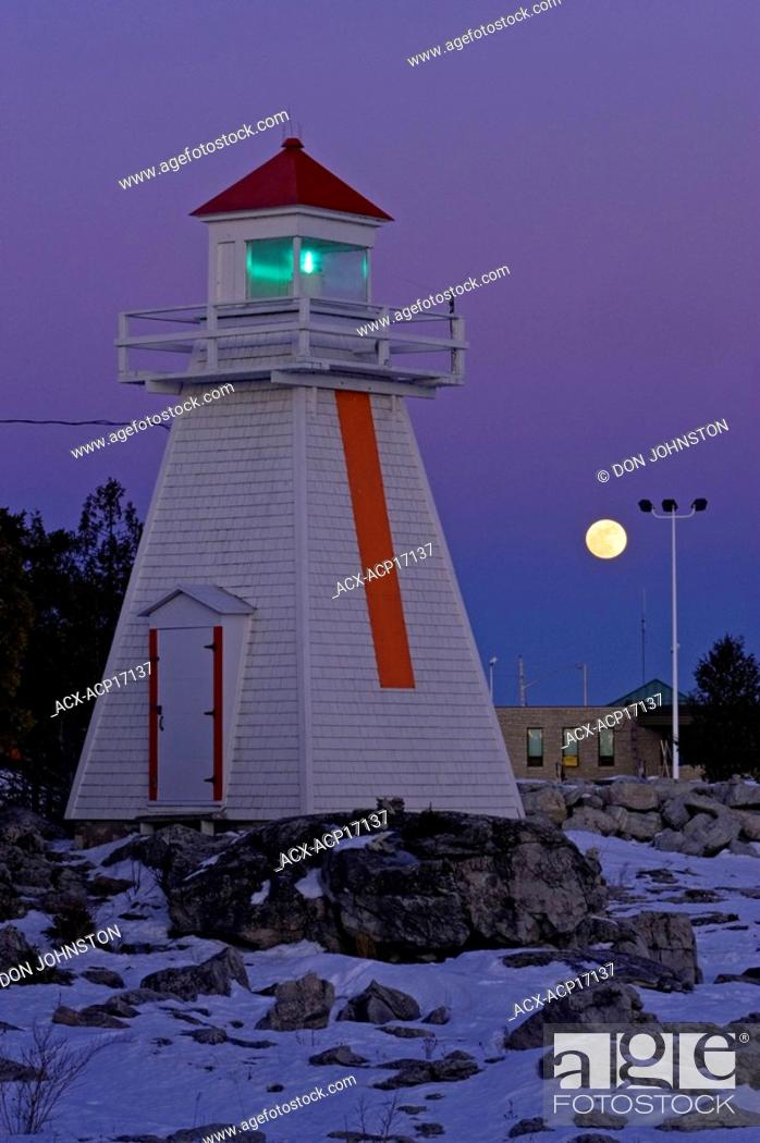 Stock Photo: Moonrise over lighthouse and ferry terminal buildings, South Bay, Manitoulin Island, Ontario, Canada.