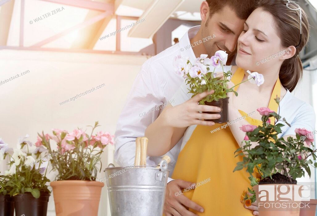 Stock Photo: Couple de-potting plants together.