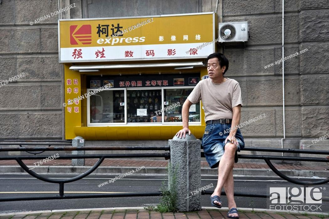 Stock Photo: A man sitting on a fence, smoking a cigarette, in front of a photo store.
