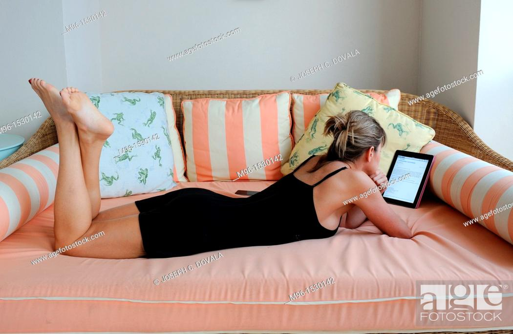 Stock Photo: Woman reading digital tablet on patio bed, Bermuda Island, Atlantic.