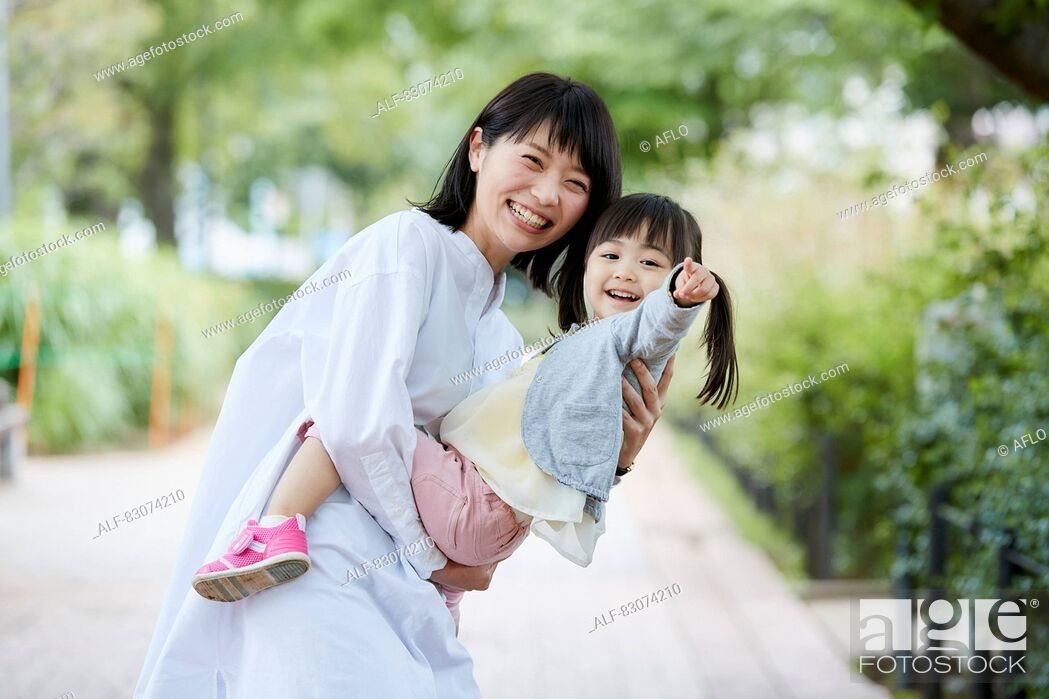 Stock Photo: Japanese mother and daughter at a city park.