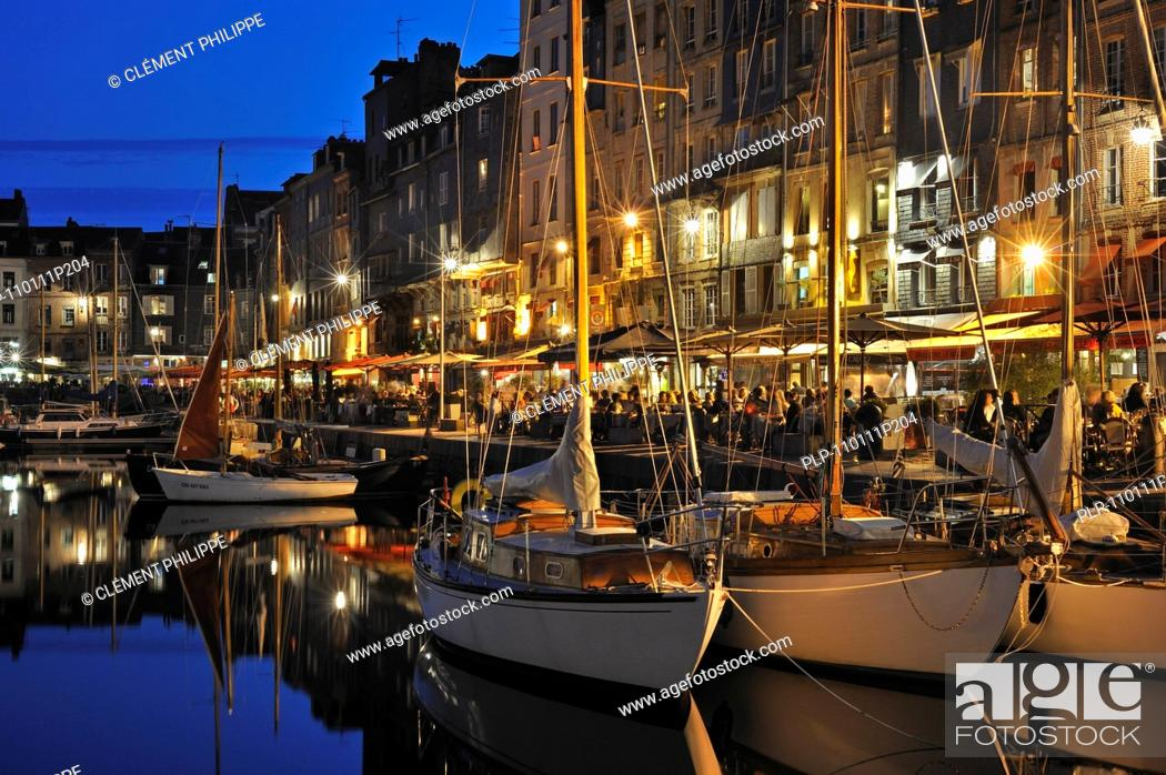Stock Photo: Sailing boats and tourists at pavement cafés / sidewalk cafes along the quay of the Honfleur harbour at night, Normandy, France.