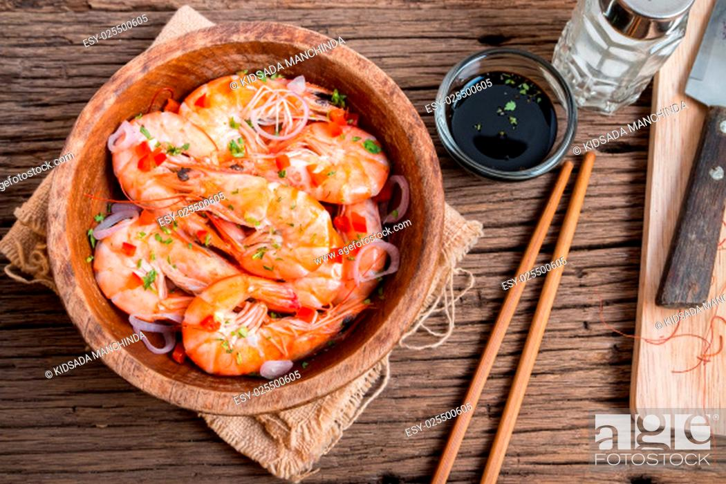 Stock Photo: steamed shrimps in a wooden bowl on wood background.