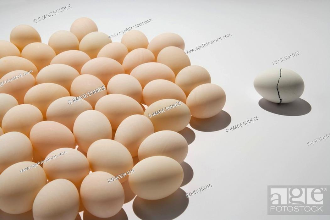 Stock Photo: A cracked egg near other eggs.