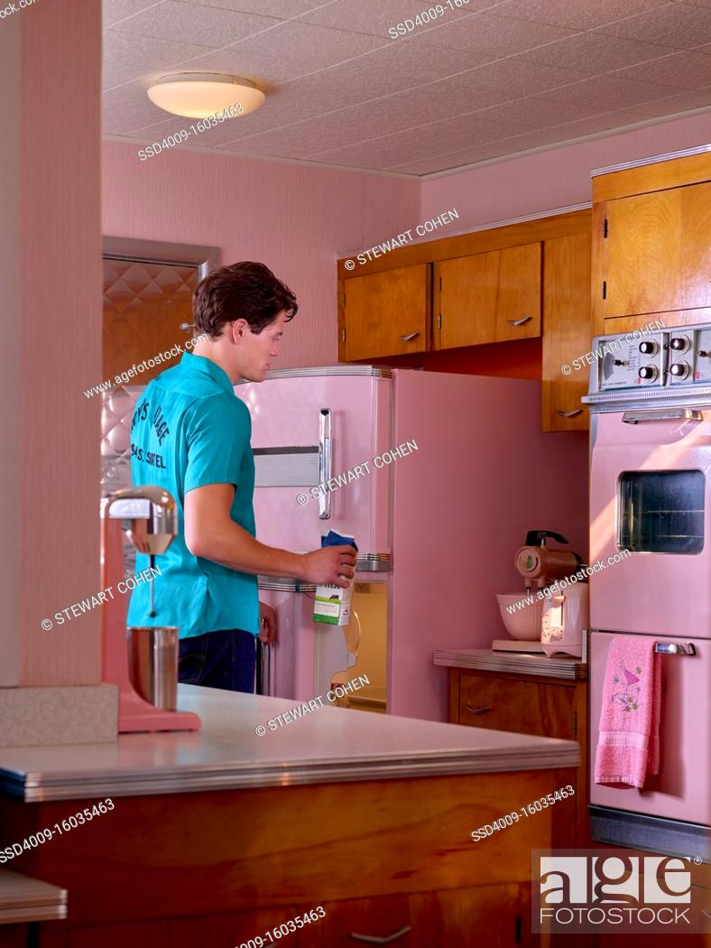 Stock Photo: Vintage styled portrait of a man taking out milk from fridge in a pink mid century kitchen.