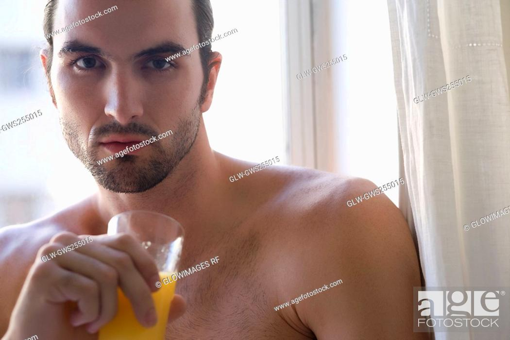 Stock Photo: Portrait of a young man holding a glass of juice and thinking.