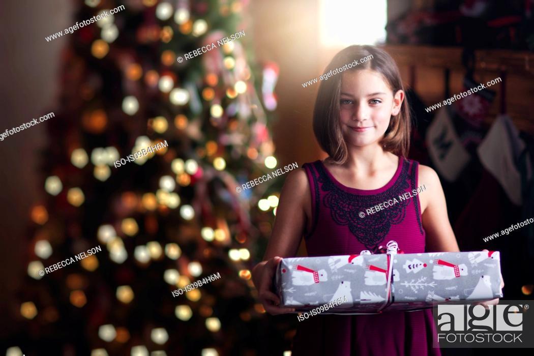 Stock Photo: Young girl holding christmas gift.