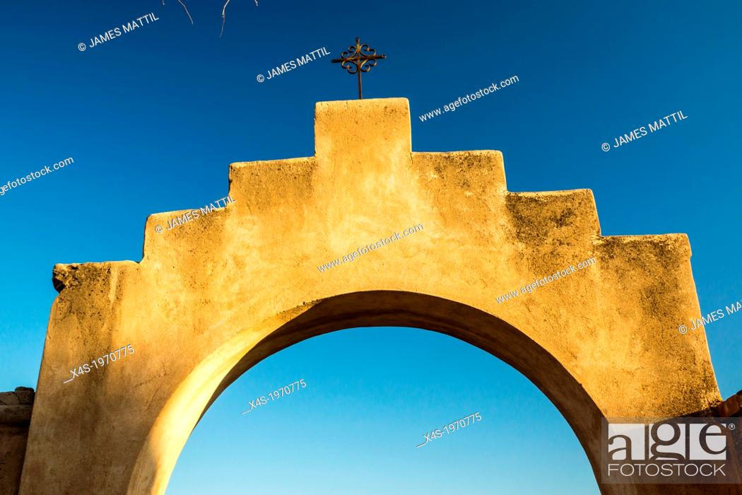 Stock Photo: An iconinc adobe arhway and crucifix at a Spanish mission in Arizona.