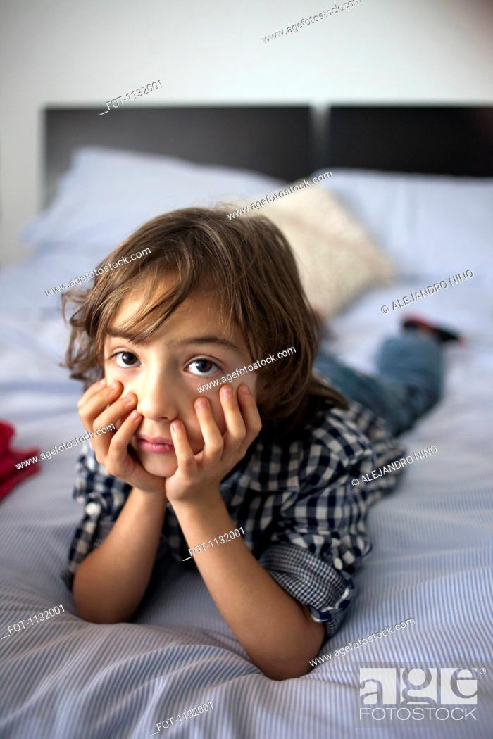 Stock Photo: A young boy lying on a bed looking sad.
