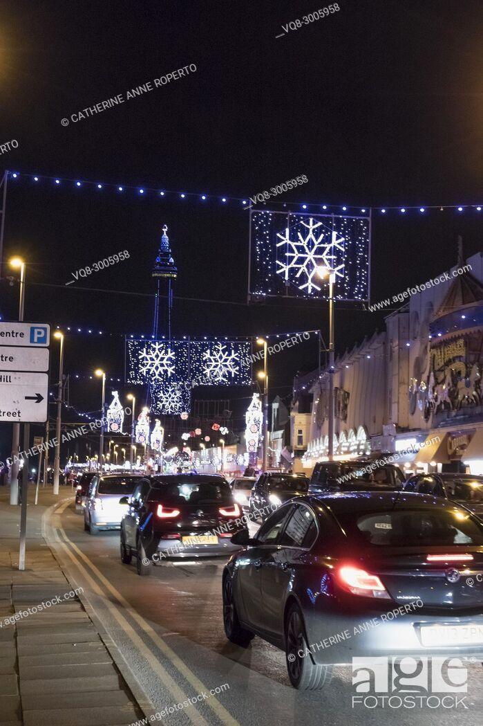 Imagen: Car tail lights driving along the Esplanade through Christmas snowflake and Big Ben illuminations towards Blackpool Tower, Blackpool, England.