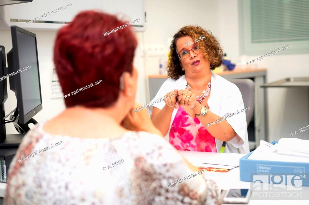 Stock Photo: Care for deaf patients in sign language, Nice Hospital, France. A patient is visiting the doctor for her husband, who is also deaf, and very dependent.