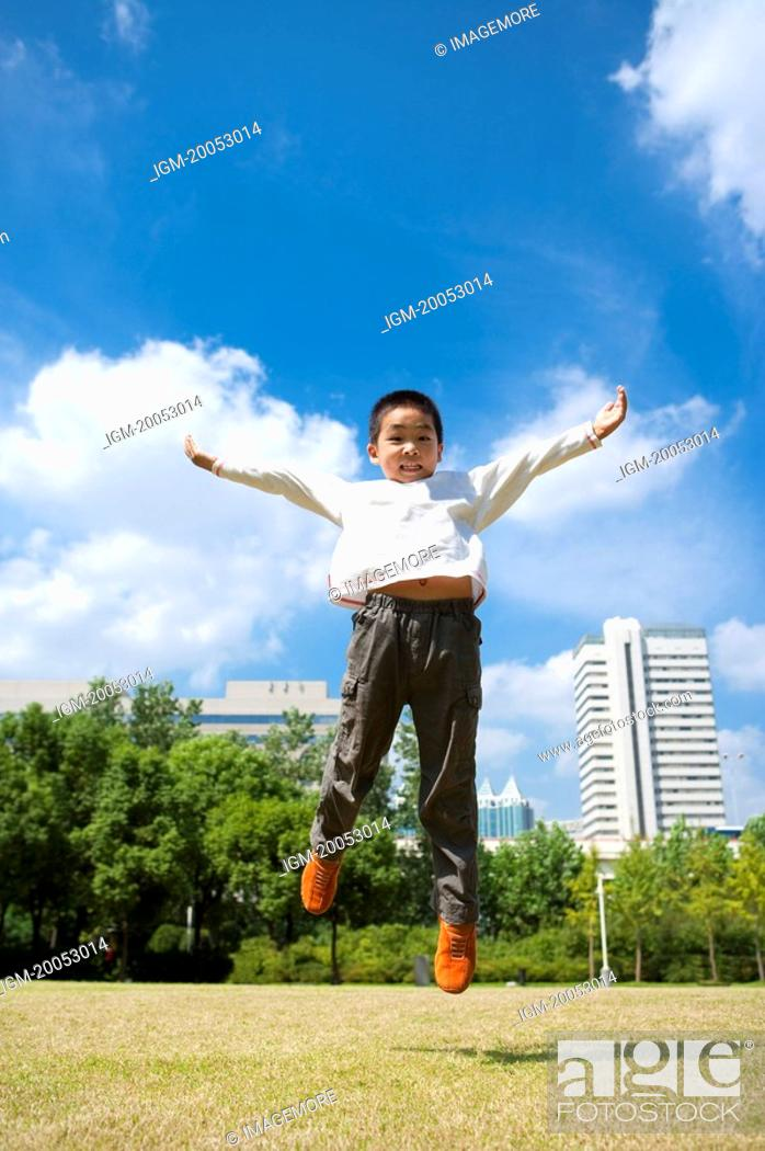 Stock Photo: Little boy jumping in mid-air with arms outstretched and looking down.