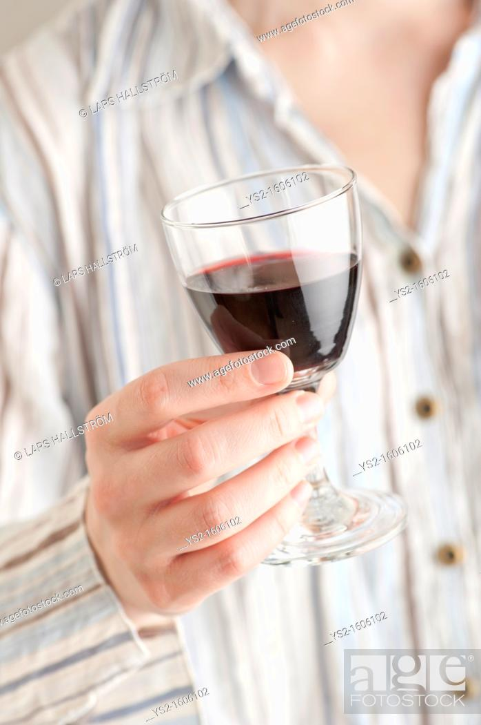 Stock Photo: Woman holding a glass of red wine.