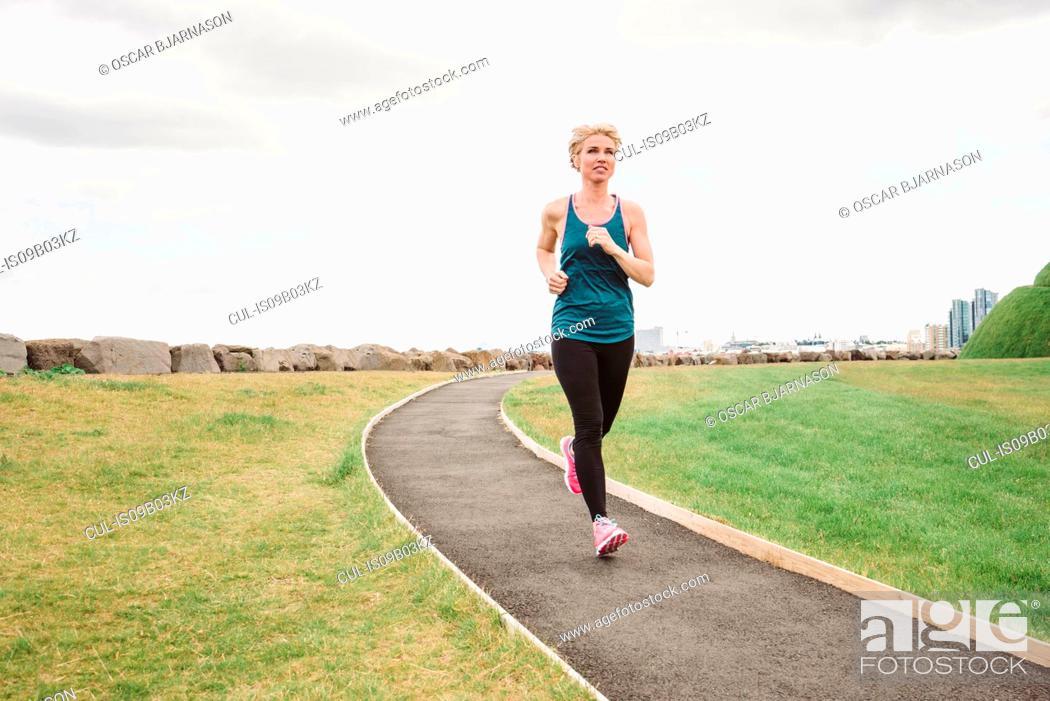 Stock Photo: Female runner running on coast path, Reykjavik, Iceland.