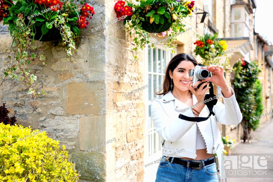 Stock Photo: Young woman on village street photographing with digital camera, Cotswolds, England.
