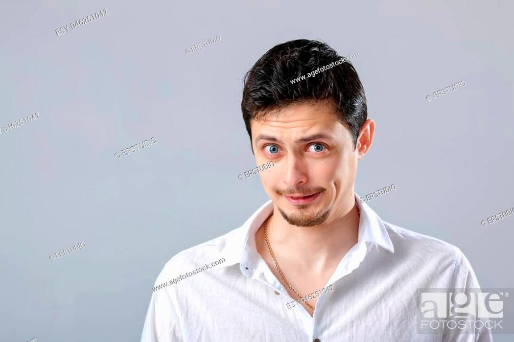 Stock Photo: handsome young frustrated and resentful brunette man in white shirt on gray background.