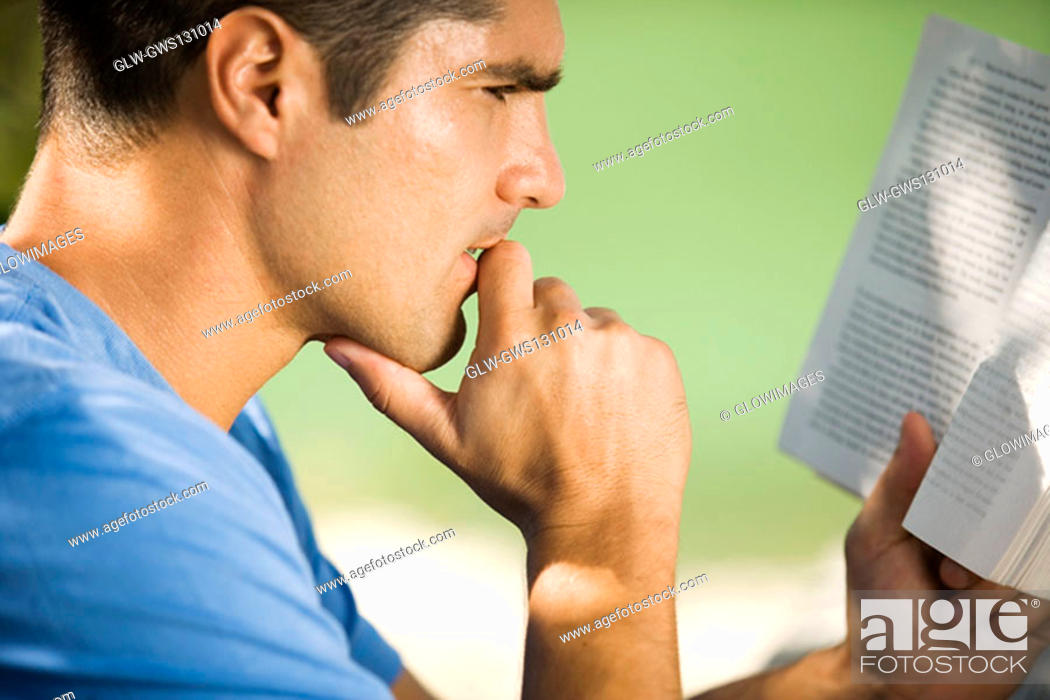 Stock Photo: Side profile of a mid adult man reading a book.