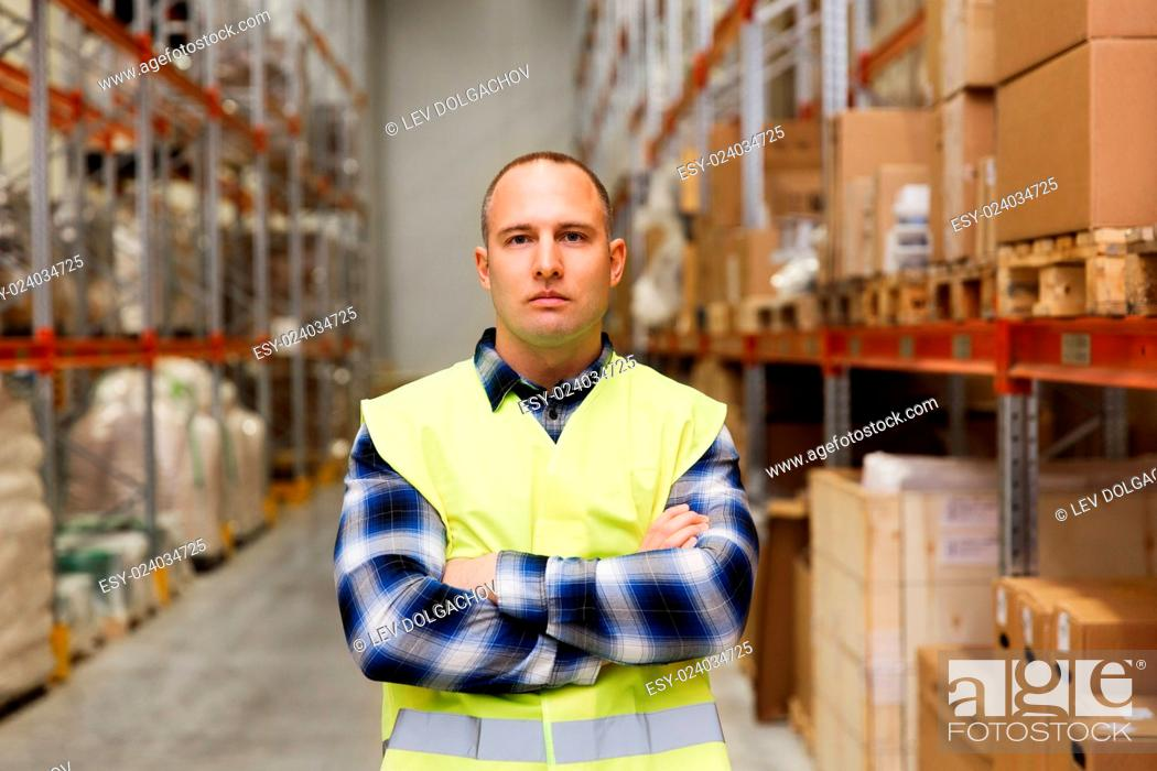 Stock Photo: wholesale, logistic, people and export concept - man in reflective safety vest at warehouse.