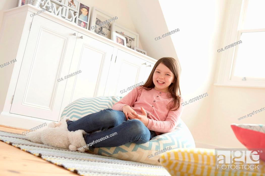 Stock Photo: Portrait of girl reclining on beanbag chair.