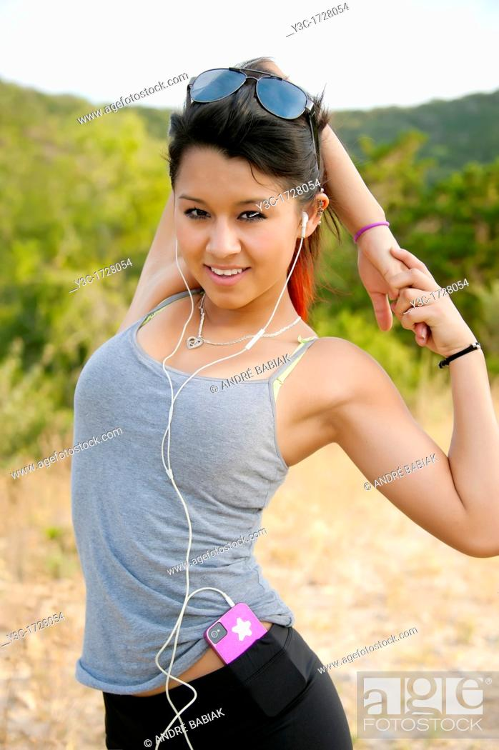 Stock Photo: 17 years old hispanic girl in fitness outfit stretching and getting ready to work out outdoors.