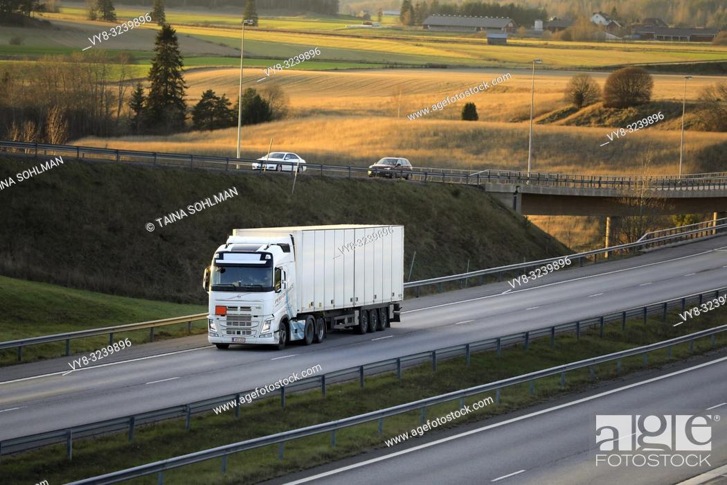 Stock Photo: Salo, Finland - November 18, 2018: White Volvo FH semi trailer driving among motorway traffic at sunset time in late autumn.