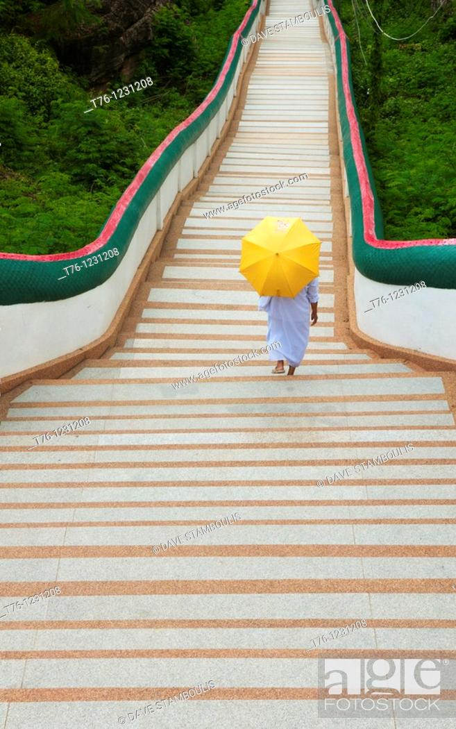 Stock Photo: nun walks down long stairs at Wat Phra Phuttabat outside of Khon Kaen, Thailand.