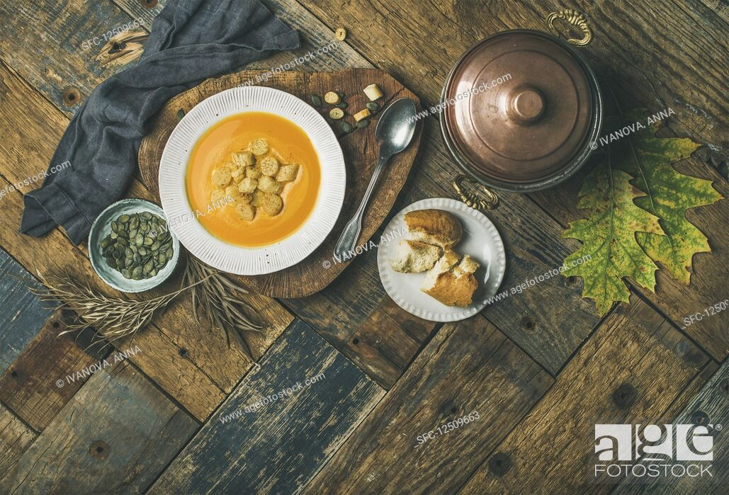 Stock Photo: Fall warming pumpkin cream soup with croutons and seed.
