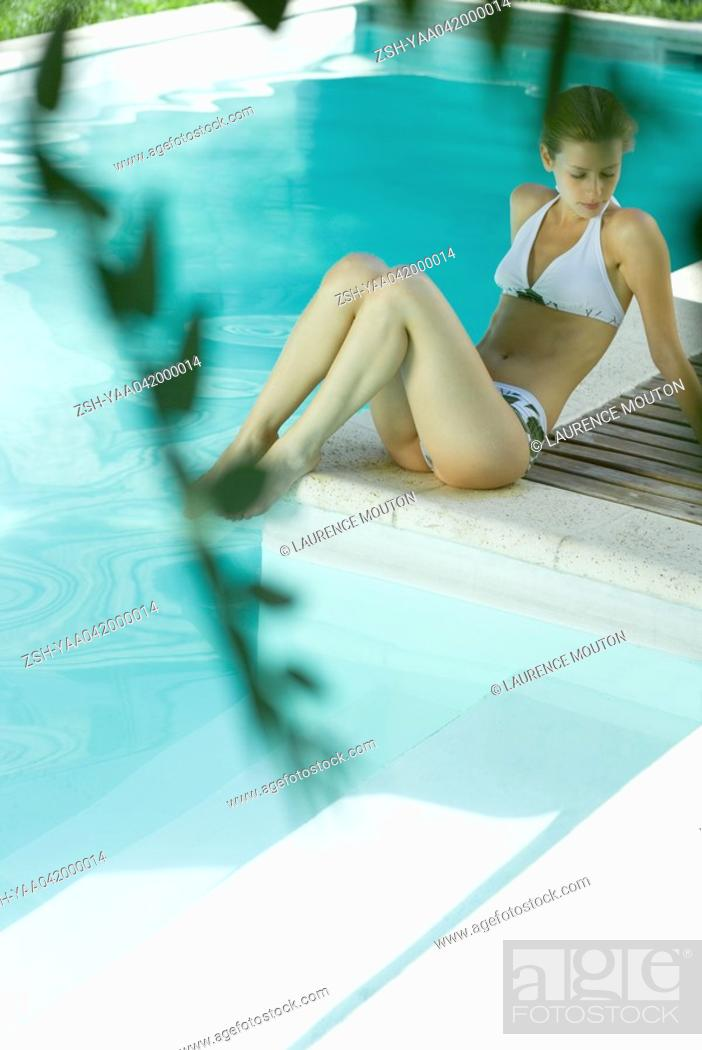 Stock Photo: Young woman sitting by pool, full length.