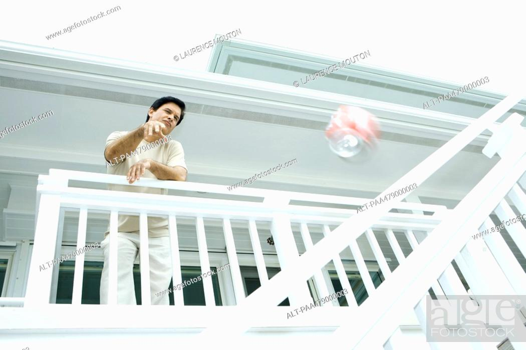 Stock Photo: Man throwing drink can from deck, low angle view.