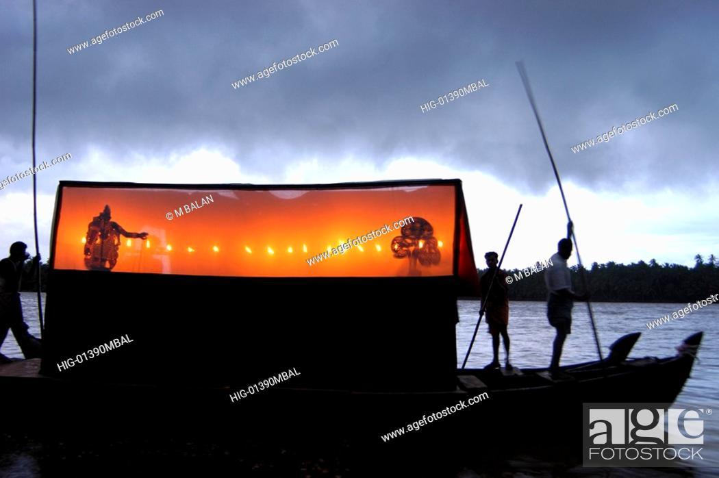 Stock Photo: THOLPAVA KOOTHU ON BOAT DURING MONSOON IN CHANDRAGIRI RIVER, KASARAGOD.