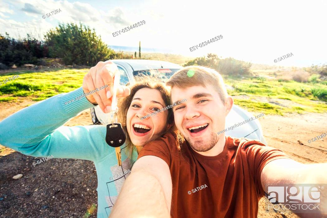 Stock Photo: portrait of happy beautiful couple showingh the keys standing near the car.