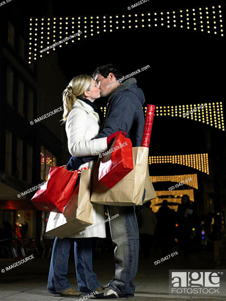 Stock Photo: Couple kissing whilst christmas shopping.