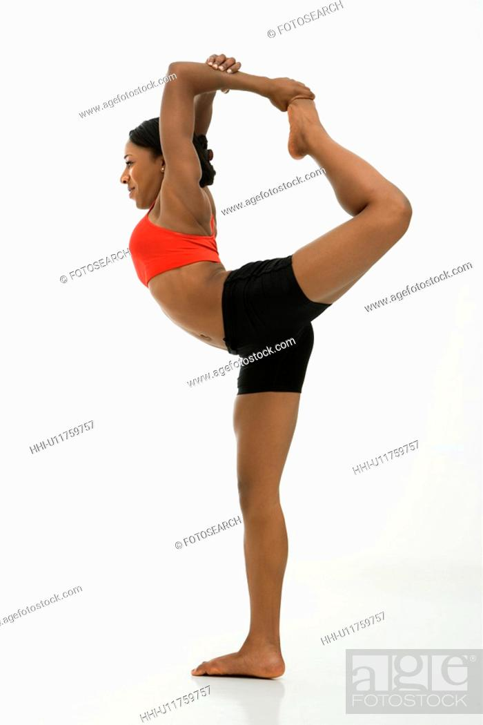 Stock Photo: Profile of African American woman in Lord of the Dance Yoga position.