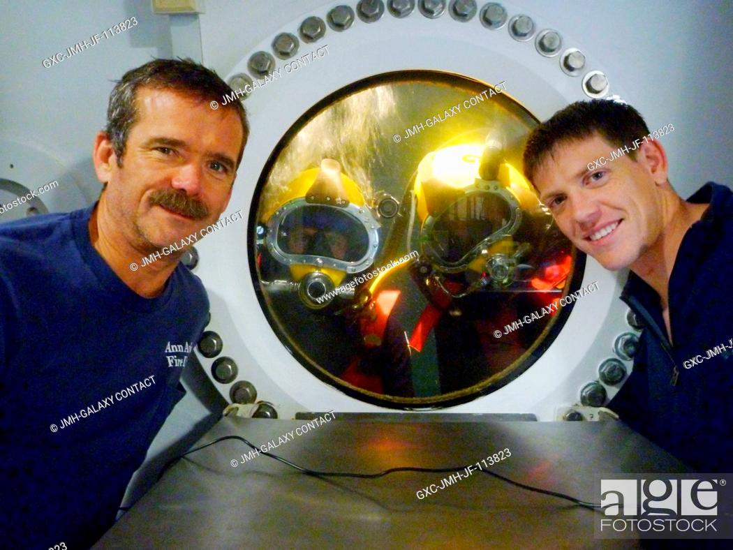 Stock Photo: NEEMO 14 crew members Chris Hadfield (left), commander, and Andrew Abercromby (right) pose for a photo with Tom Marshburn and Steve Chappell who are.