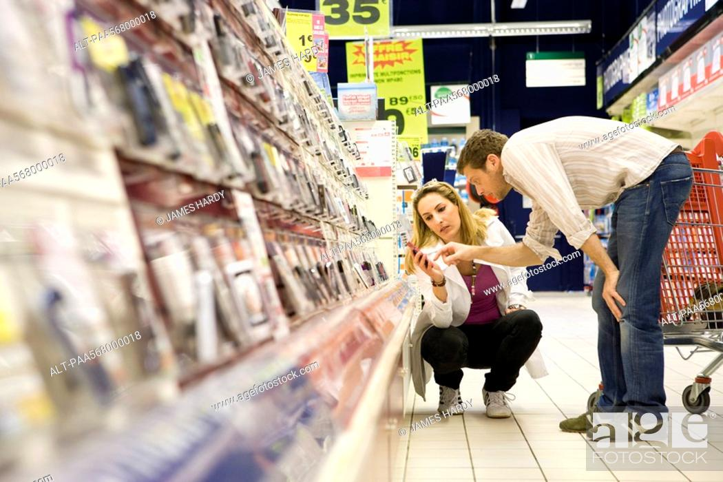Stock Photo: Couple selecting cell phone from store display.
