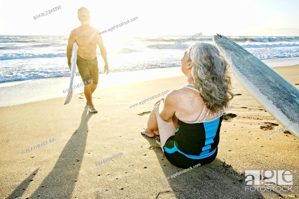 Stock Photo: Older Caucasian couple on beach with surfboards.