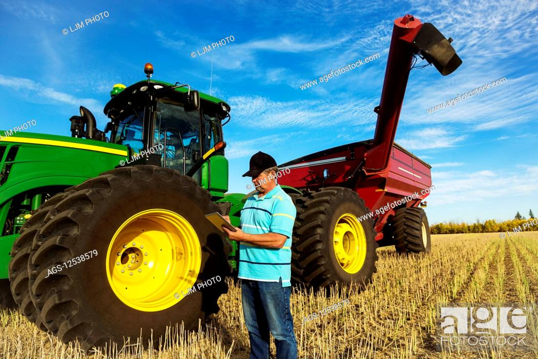Stock Photo: Farmer standing in a canola field beside a tractor with a wagon and using a tablet to assess his yield from the harvest on a warm fall evening; Edmonton.