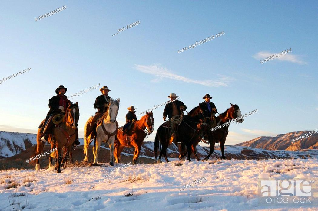 Stock Photo: Wranglers leading their horses over the snowcaped ranges of wyoming at sunset.