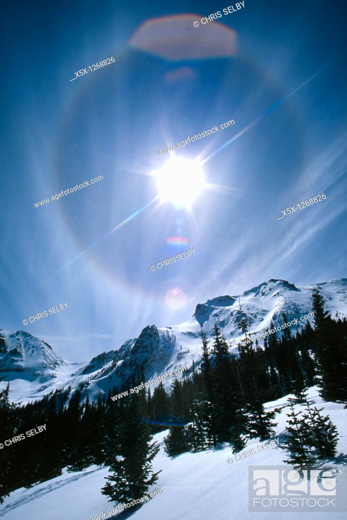 Stock Photo: Sundog and lens flare in sky over Never Summer mountains in winter, Colorado, USA.