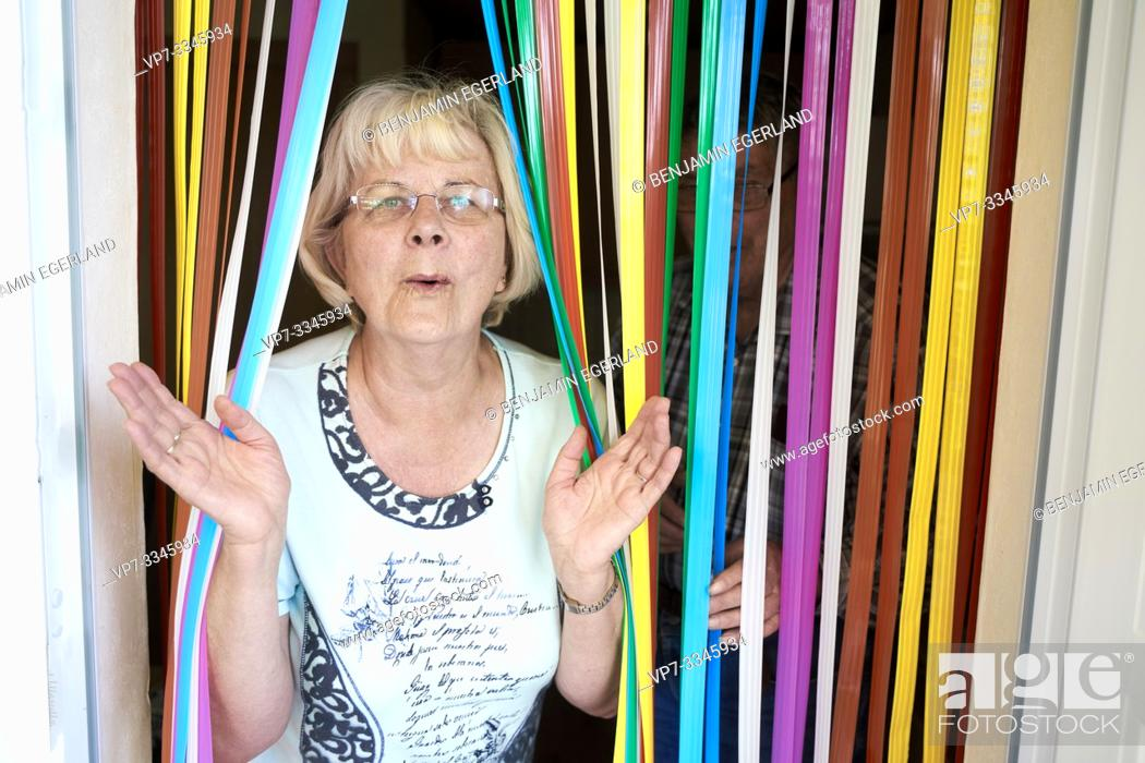 Imagen: funny senior woman walking through colorful curtain stripes at home, clapping hands.