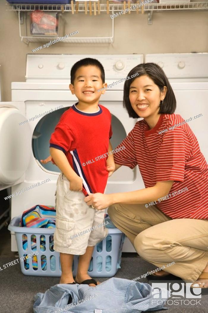 Stock Photo: Asian mother and son with clean laundry next to dryer.