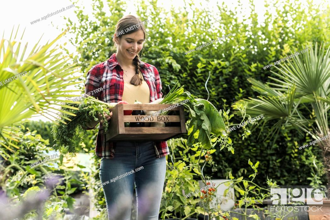 Stock Photo: Smiling young woman carrying vegetables in crate while standing amidst plants at garden.