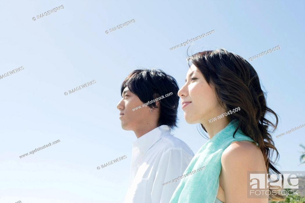Stock Photo: Profile of a young couple standing together.