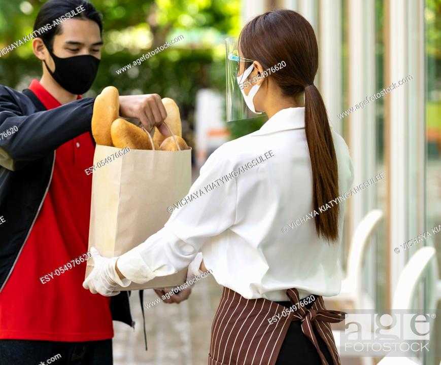 Stock Photo: Deliverly asian bike man pick up bakery grocery bag from bakery shop to deliver to customer who make online order. Food deliverly service concept in new normal.